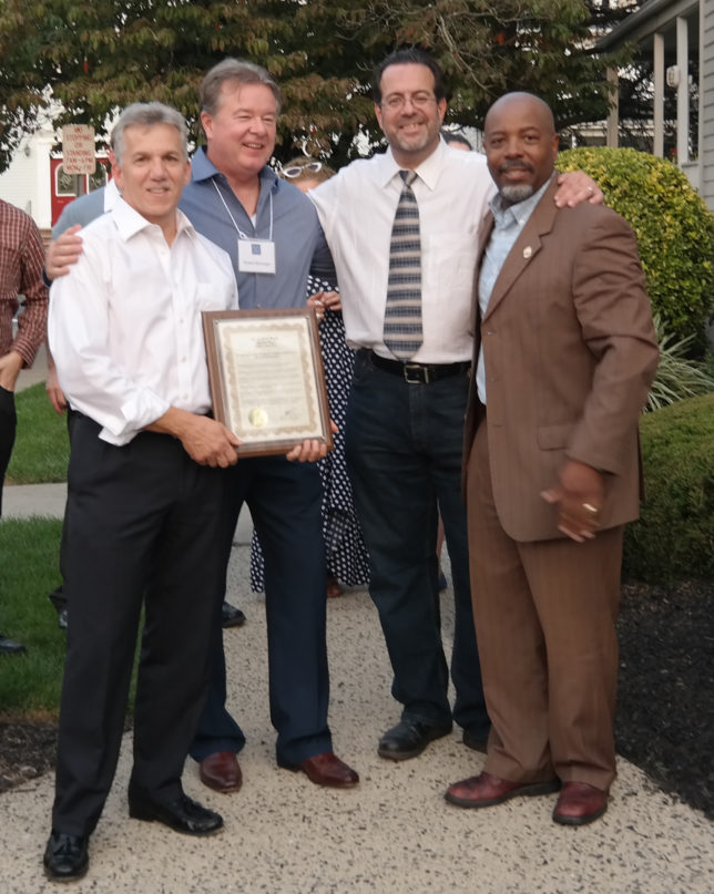 Pictured (left front to right): Firm partners Robert M. Longo, AIA, Robert F. Barranger, AIA and Michael G. Soriano, AIA, receive a special proclamation from Borough Council President Derryck C. White.